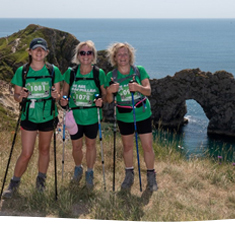 Three women standing in front of Durdle Door, Dorset.
