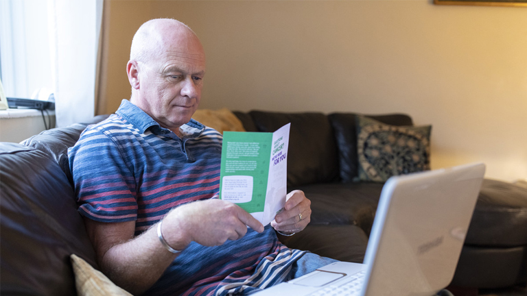 A man sits on a sofa reading a cancer information leaflet, a laptop is open on his lap.