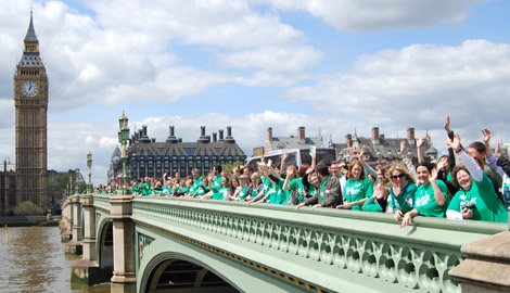 People wearing Macmillan t-shirts standing and waving on Westminster Bridge.