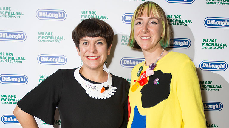 Two female designers (Rosie Wolffenden and Harriet Vine) who make up the label Tatty Devine, stand smiling.