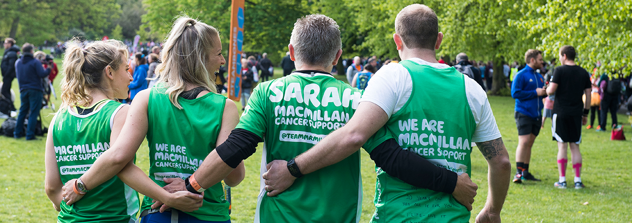 Two men and two women in Macmillan kit walk with their arms around eachother in solidarity.
