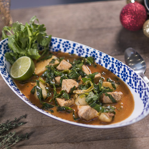 A dish of thai massaman curry with turkey and potatoes that is surrounded by Christmas decorations.