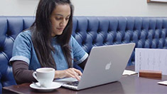 An image of a young woman sitting using a laptop.