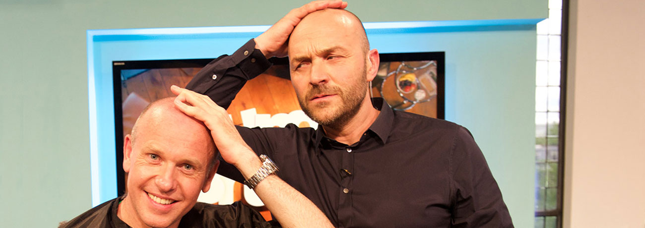 Tim Lovejoy and co-presenter rubbing their newly shaved heads.