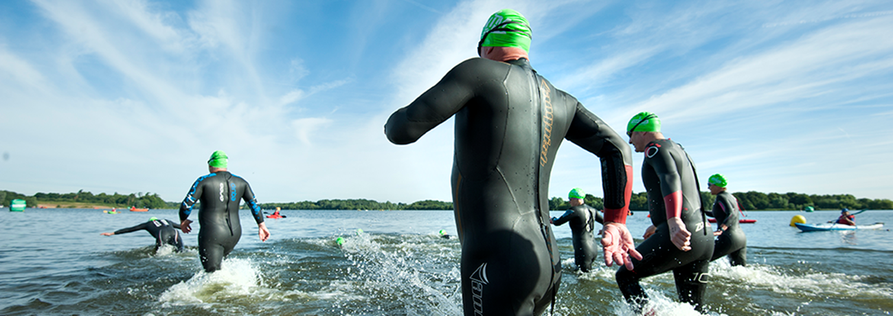 A group of athletes running into open water wearing trisuits and green swim caps.