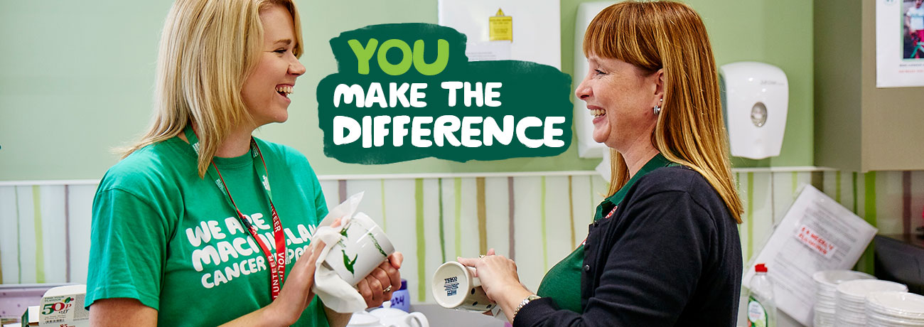 Two Macmillan volunteers chatting and drying mugs in a kitchen. Overlaid text reads, 'You make the difference.'
