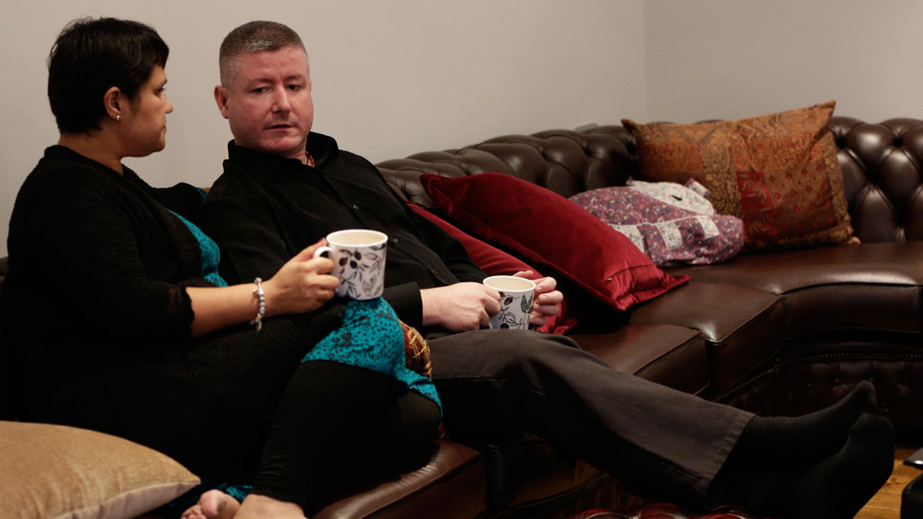Waheed and husband Anthony sit on the sofa together in their family home.