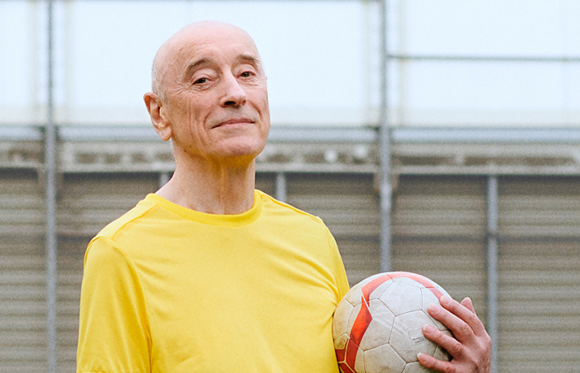 A man poses for a picture on a football pitch. He is holding a football and wearing a yellow t-shirt.