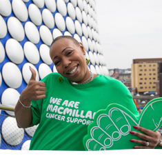 A supporter smiling with her thumb up, holding a large green foam finger in front of the Bull Ring, Birmingham.