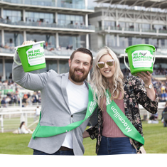 Supporters smiling with green buckets at Macmillan Charity Raceday in York.