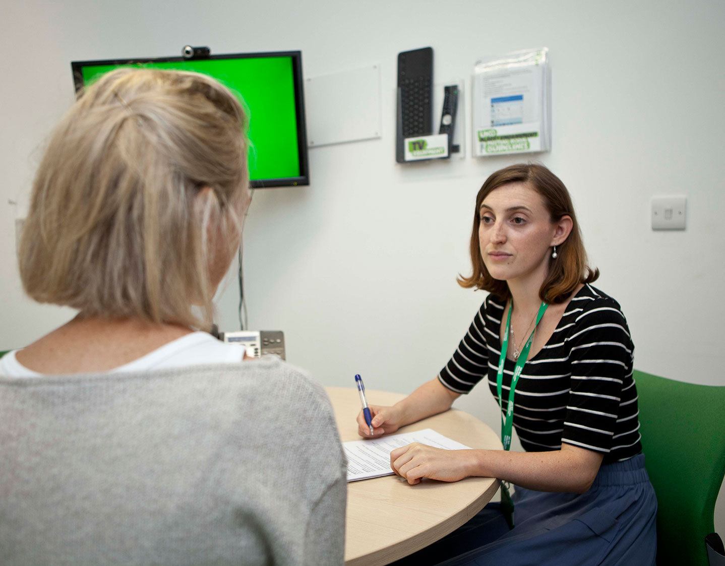 A female member of Macmillan staff interviews a woman in an office.