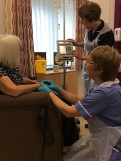 Nurses look after a patient in their own home, one of the project's aims.