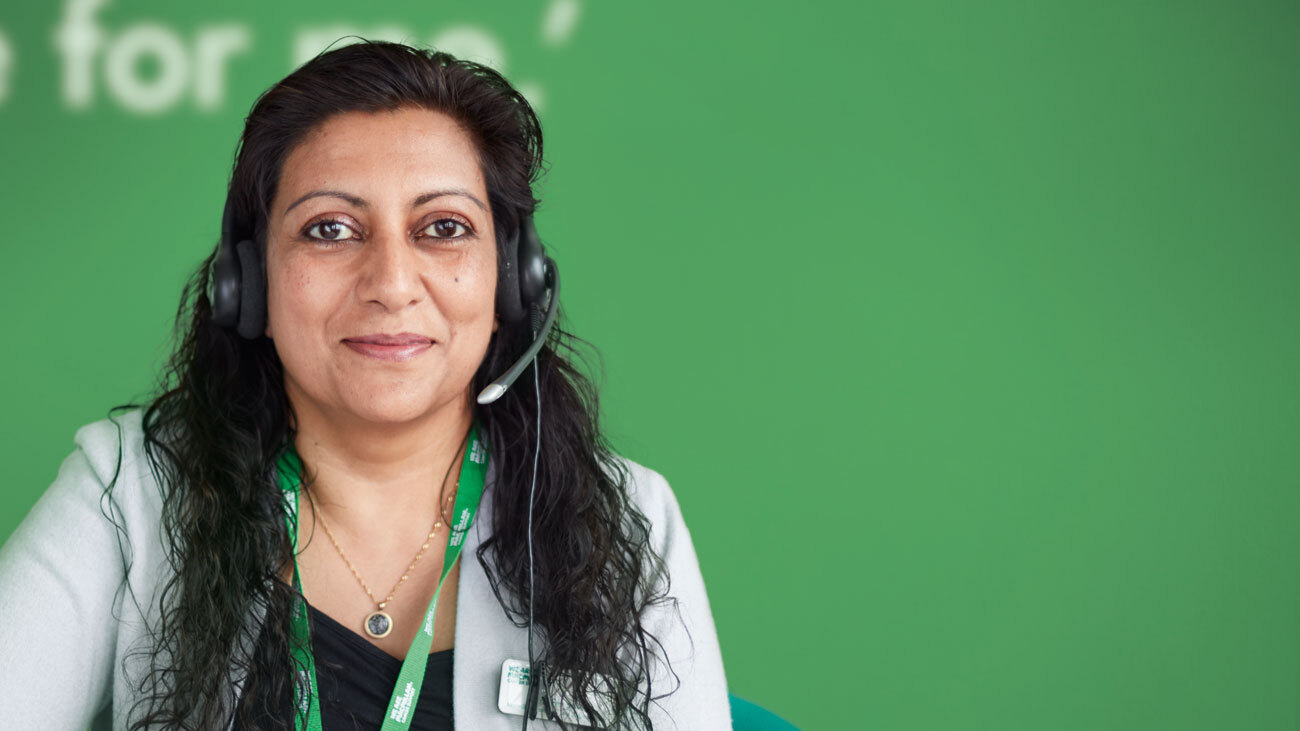 Maria, a Cancer Info & Support Officer in her 40s, wearing a headset.