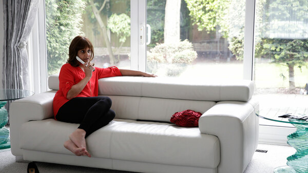 Ravinder sits on a white sofa with the phone to her ear. She is wearing black trousers and a red top. She appears to be in her living room.