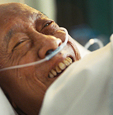Image of a smiling man in a hospital bed with an oxygen tube
