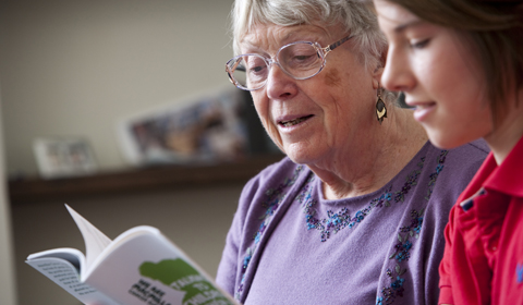 Two women look at a Macmillan cancer information booklet in a support centre
