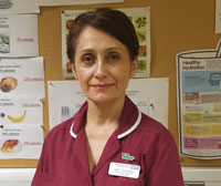 A nurse in a burgundy uniform wearing an NHS name tag and Macmillan badge.