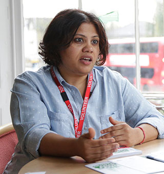 A female volunteer called Usha sits talking. She wears a red lanyard and there is a window directly behind her through which a London bus can be seen passing.