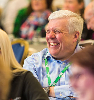 A man sits at a conference, he is laughing at a joke.