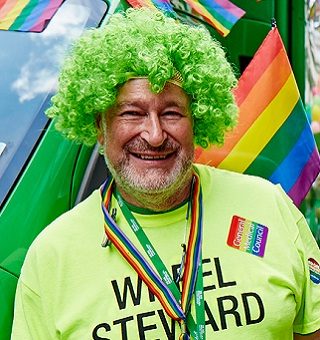 A male volunteer in a green curly wig smiles at the Pride parade
