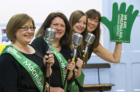 Four members of the theatre group Showcase, holding microphones and waving a large green Macmillan foam hand.